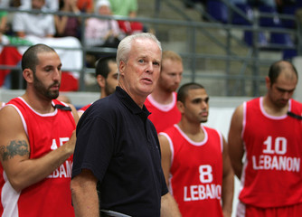 Lebanese national basketball team members stand with US coach Coughter in Amman