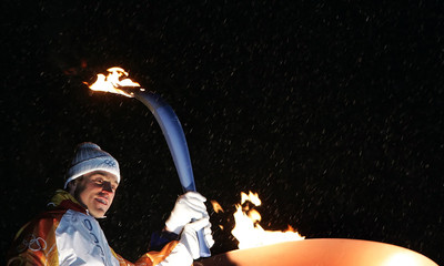 Italy's Christian Ghedina holds the Winter Olympic torch at Cortina d?Ampezzo