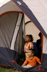 Children stand in a tent at a field used as temporary refuge for earthquake survivors in Laguna of Fraijanes