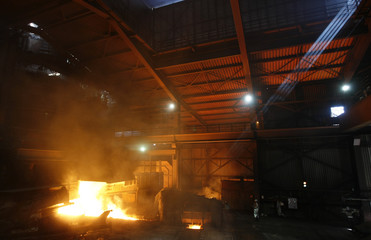 A beam of light inluminates the smelting furnace of ArcelorMittal steel manufacturer plant in Eisenhuetten