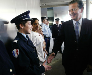 France's Justice Minister Perben shakes hands with police during visit to UHSI, a specialised secure ...