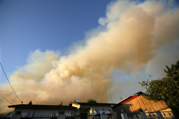 Residents watch from their roof during the Station Fire in La Crescenta area of Los Angeles