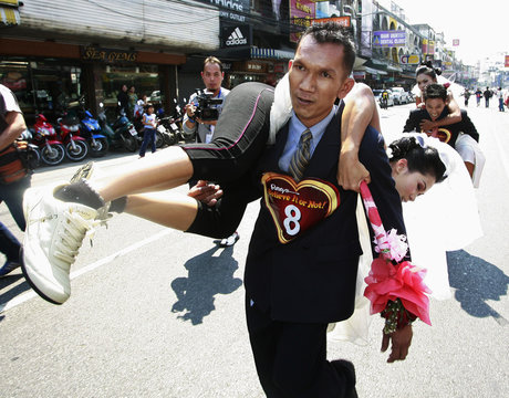 """A groom carries his bride on the back during the """"True Love... Fears No Distance"""" race on Valentine's Day in Pattaya"""