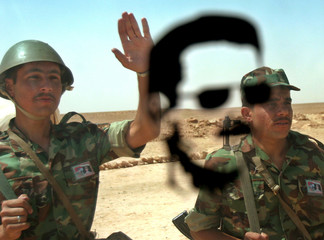 Syrian border officials wave near the vast Iraqi-Syrian desert border, as a picture of Syrian Presid..
