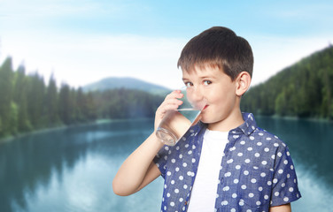 Little boy with glass of clean water on landscape background