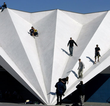 """TEENAGER ENJOY THE SUN ON TOP OF A ROOF AT BERLIN'S FAMOUS """"ALEXANDER PLATZ"""" SQUARE."""