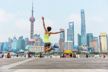 Wall Mural - Happy fitness woman jumping of joy and success in Shanghai skyline in goal achievement challenge. Life goals. Weight loss or exercise winning concept.