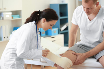 Orthopedist applying bandage onto patient's knee in clinic
