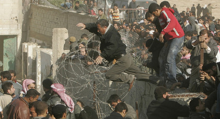 Palestinians leap into Egypt from the destroyed section of the border wall between the Gaza Strip and Egypt