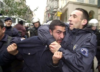 TURKISH POLICE HOLDS PROTESTER IN A HEADLOCK IN ISTANBUL.