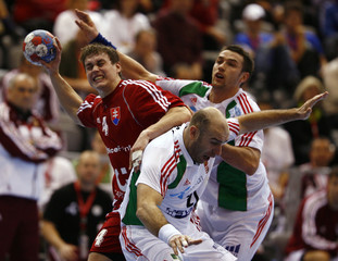 Slovakia's Kukucka fights for a ball with Hungary's Ilyes and Herbert during their Men's World Handball Championship match in Osijek