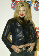 "Actress Natasha Henstridge displays her Rolling Stone logo belt buckle as she arrives at the ""Fashio.."