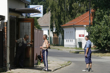 Residents stand in front of a  workshop in the village of Eisenhuettenstadt