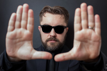 A serious man with a beard and a stylish hairstyle carries out framing with his hands. Directed in a business black suit and sunglasses