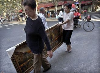 Local women carry a painting in a street in downtown Shanghai