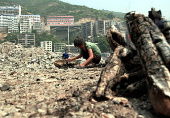 WOMAN COLLECTS CHARCOAL IN TOWN TO BE SUBMERGED BY CHINAS THREE RIVERS DAM