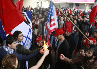 Lebanese Communist party members set a U.S flag on fire during a protest  in front of the United Nation headquarters in Beirut