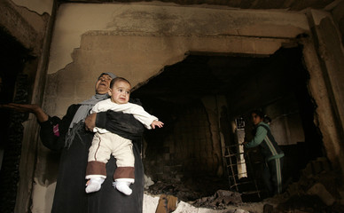 A Palestinian woman gestures inside her home after fighting between Hamas and Fatah in Gaza