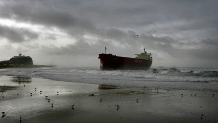 A helicopter flies over the stranded 40,000 tonne coal ship Pasha Bulker about 100 metres from Nobbys Beach