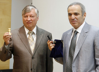Former chess world champions Kasparov and Karpov pose with their chess figures at a news conference in Valencia