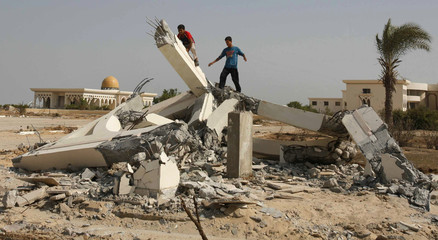 Palestinians play on the rubble of a destroyed part of Gaza international airport following an Israeli raid in the southern Gaza