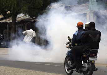 A man runs from tear gas as a motorcyclist and his passengers pass by the gas after riot police were called in to disperse protesters shouting abuse at men on trial for dressing as women in Bauchi, northern Nigeria