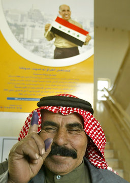 An Iraqi man shows his right index finger stained with blue ink after casting his vote in Amman.