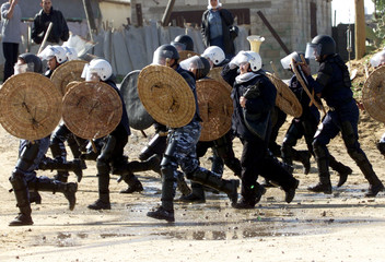 Palestinian policemen clash with stone throwers during clashes near [Hamas founder Sheikh Ahmed Yass..