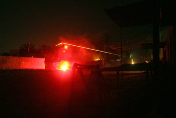 U.S soldiers fire rifles and a grenade launcher at insurgents during a night mission in Baquba