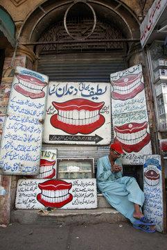 Roadside dentist Mohammad Sharif works on a denture at his makeshift clinic in Karachi