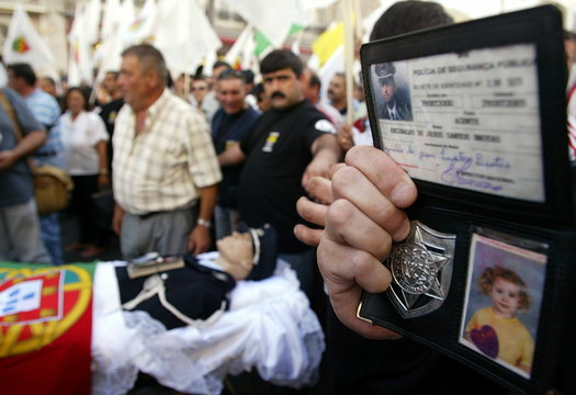 A policeman displays his police badge and ID card during a demonstration in downtown Lisbon, June 22..