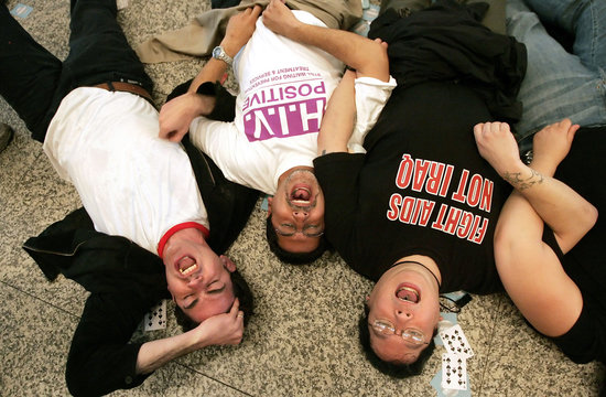 AIDS activists chant after chaining themselves together and lying on the floor of the lobby of the o..