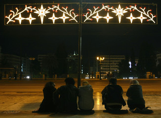 Demonstrators sit below a Christmas decoration during a peaceful protest outside Greece's parliament in Athens