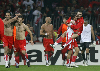 Players of Olympiakos Piraeus celebrate after defeating Werder Bremen during their Champions League Group C soccer match at the Weser stadium in Bremen