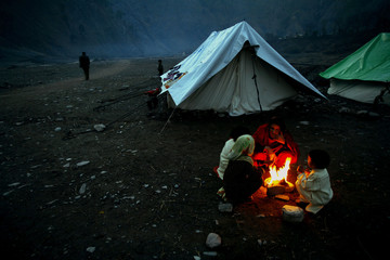 Kashmiri women and children try to keep warm at Mustafai relief camp in outskirts of Muzaffarabad