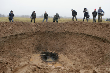 Locals look into a crater in field near Mazsalaca