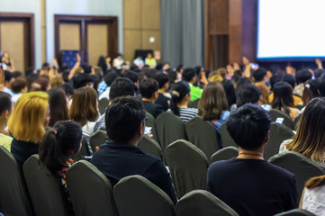 Speaker on the stage with Rear view of Audience in the conference hall or seminar meeting, business and education concept