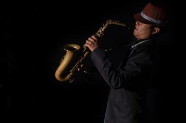 A saxophone player in a dark background, black and white tone