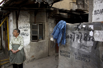 An elderly woman stands at the entrance to her house which is due to be demolished in the coming weeks as she looks on a development project on the opposite street in Shanghai