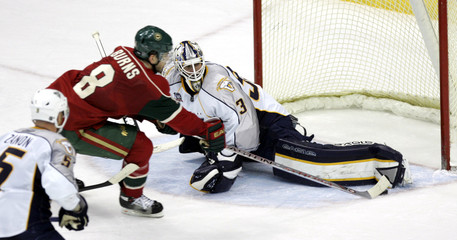Predators goalie Mason saves shot by Wild's Burns during their NHL hockey game in Minnesota