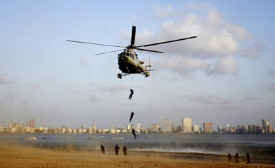 An Indian navy MI-17 helicopter drops commandos at the sea front during a demonstration, which was part of an unveiling ceremony for the official mascot of the 4th World Military Games, in Mumbai