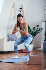 Sporty athletic woman exercising with rubber tape