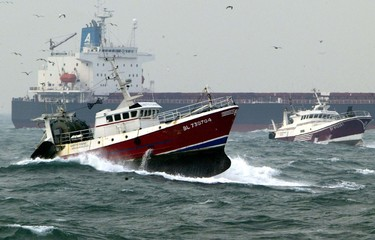 A freighter avoid the French fishermen stage a go-slow operation with their trawlers travelling at j..