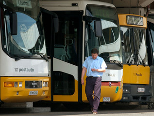 A DRIVER WALKES BY PARKED BUSES IN VIENNA.