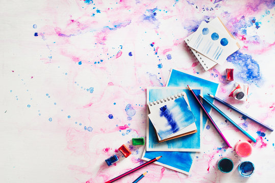 Feminine artist workplace with watercolor and sketches