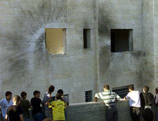 PALESTINIANS LOOK AT THE DAMAGED FATAH OFFICE IN RAMALLAH.