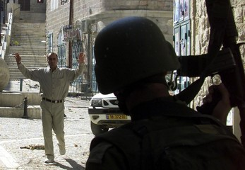 A PALESTINIAN MAN APPROACHES WITH ISRAELI PATROL DURING LIFT OF CURFEWIN BETHLEHEM.