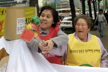 A FORMER COMFORT WOMAN SMASHES A SYMBOL REPRESENTING A JAPANESE HISTORY BOOK DURING A PROTEST ...