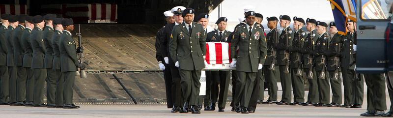 Honour guards carry the coffin with the remains of a killed U.S. soldier after its arrival from Afgh..