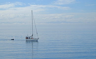 Sailboat gliding with calm blue ocean water with blue sky background and has copy space room